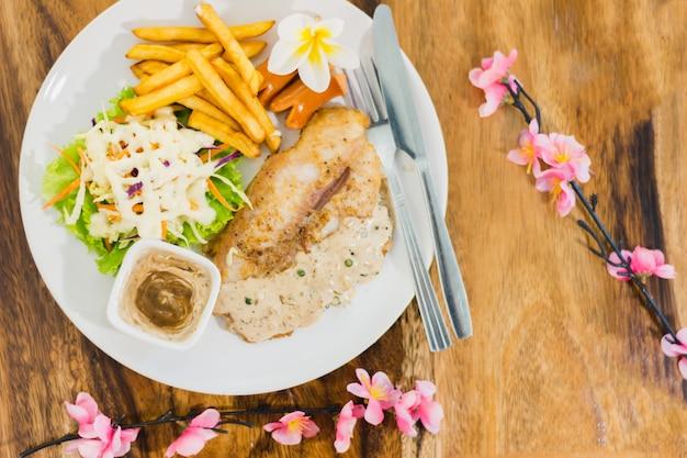 Stek wołowy z grilla i ziemniaki i sałatka na talerzu, widok z góry