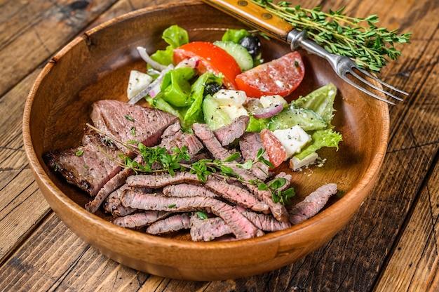 Stek wołowy z grilla kotlet rumsztyk na drewnianym talerzu z sałatką warzywną