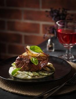 Stek wołowy z puree ziemniaczanym i szparagami na czarnym talerzu. kolacja w restauracji
