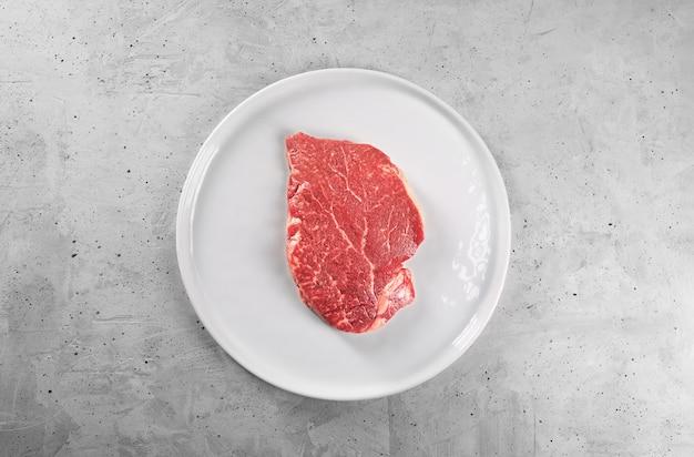 Stek wołowy z rozmarynem i pieprzem na białym talerzu z kopią miejsca