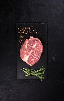 Stek wołowy z rozmarynem i pieprzem na czarnym stole z miejscem na kopię, orientacja pionowa