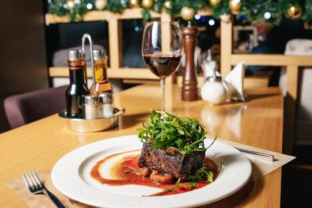 Stek wołowy z rukolą i pieczarkami na białym talerzu na stole w restauracji.