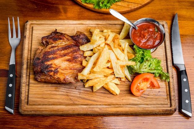 Stek wołowy z sosem pieprzowym i grillowanymi warzywami na deski do krojenia ciemne drewniane tła
