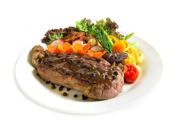 Stek wołowy z sosem z czarnej papryki zdobi świeży rozmaryn, grillowany boczniak z brokułami