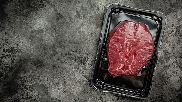 Stek wołowy zamknięty próżniowo, gotowy do gotowania. . wyroby mięsne pakowane na czarnym tle, półprodukt mięsny. widok z góry.