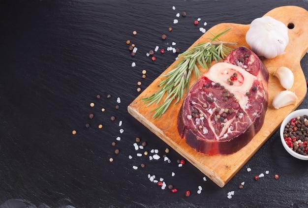 Stek wołowy ze świeżego surowego mięsa z kością z przyprawami, rozmarynem, czosnkiem i oliwą z oliwek na drewnianej desce do krojenia i na czarnej powierzchni łupkowej. składniki do gotowania.
