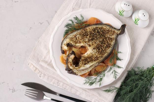 Stek z białej ryby morskiej z cebulą, marchewką i koperkiem na białym talerzu. widok z góry