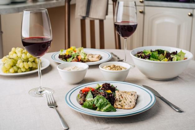 Stek z białej ryby z surówką warzywną, sosem, hummusem, winogronami i lampkami wina. podawany dla dwóch osób w kuchni