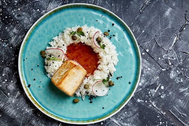 Stek z dorsza z ryżem i sosem na niebieskim talerzu na powierzchni betonu