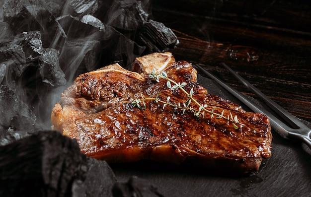 Stek z grilla na czarnej desce z łupków z widelcem do mięsa i węglami grillowymi