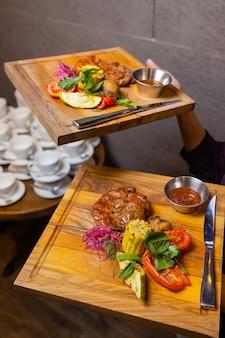 Stek z grilla rostbef i sos pieprzowy na deska do krojenia na ciemnym tle drewnianych.