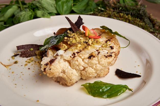 Stek z kalafiora z ziołami i przyprawami na białym talerzu.