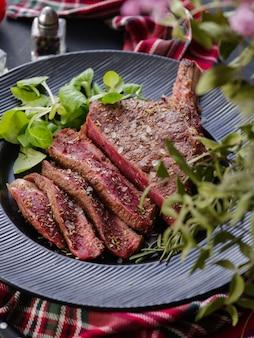Stek z kością. oko żebra. stek tomahawk na czarnym talerzu z rozmarynem. pieczenie - rzadkie. antrykot.