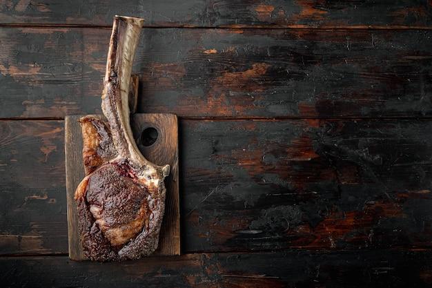 Stek z kością. stek tomahawk świeżo grillowany suchy zestaw do grillowania w wieku na sucho, na drewnianej desce do serwowania, na starym ciemnym tle drewnianego stołu, widok z góry płasko leżący, z miejscem na tekst
