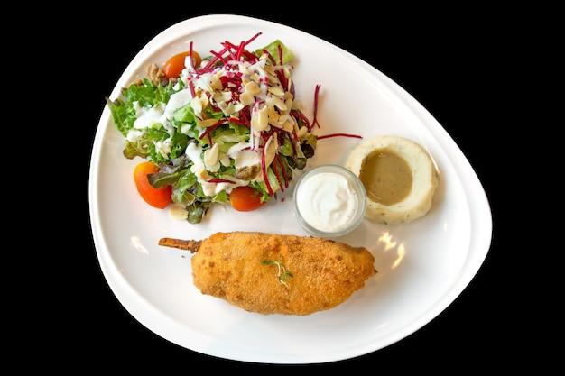 Stek z kurczaka i sera z tłuczonymi ziemniakami i warzywami mieszanymi, ostrość selektywna.