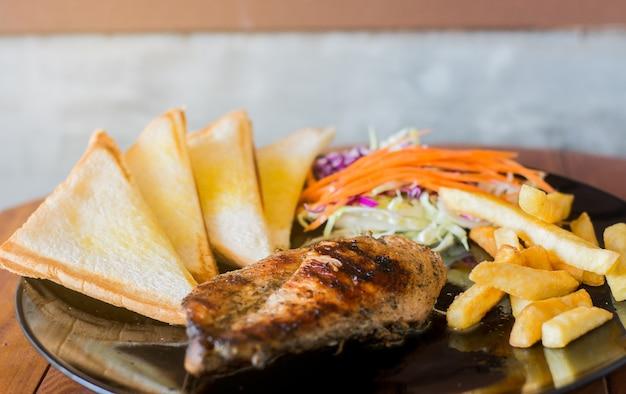 Stek z kurczaka ze smażonymi składnikami i pysznymi sałatkami.