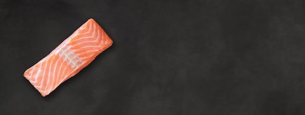 Stek z łososia na białym tle na czarnym tle płyty betonowej. widok z góry. baner poziomy