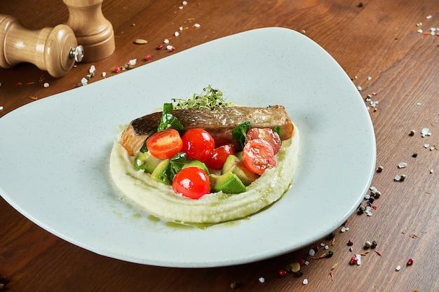 Stek z łososia na poduszce tłuczonych ziemniaków z awokado i pomidorami koktajlowymi w białym talerzu na drewnianym stole.