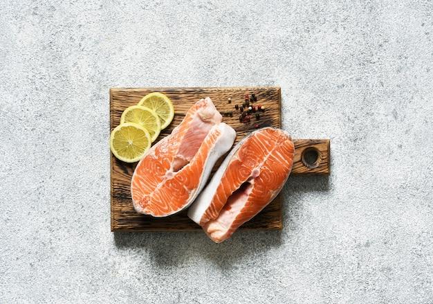 Stek z łososia surowa ryba z przyprawami przygotowanymi do gotowania. widok z góry na jasnym, betonowym tle.