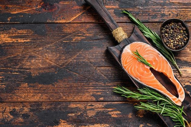 Stek z łososia surowej ryby przygotowany do gotowania na desce do krojenia. ciemne tło drewniane. widok z góry.