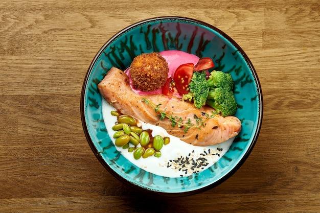 Stek z łososia w misce z białym sosem, pomidorkami koktajlowymi, fasolką szparagową i brokułami na drewnianym tle