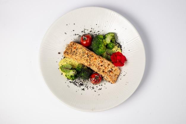 Stek z łososia w połączeniu ze smażonymi brokułami, pieczonymi pomidorkami i sosem śmietanowym na białej powierzchni