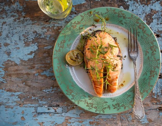 Stek z łososia z grilla ze szklanką wody, kolacja. zdrowe jedzenie. widok z góry