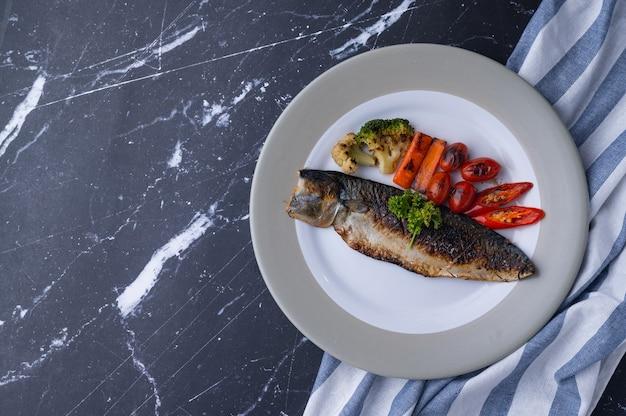 Stek z makreli pacyficznej grillowany z sideish brokułami, marchewką, pomidorem, chili i pietruszką na ceramicznym naczyniu, marmurowy stół, ciemne czarne tło, koncepcja stylizacji żywności, kuchnia domowa