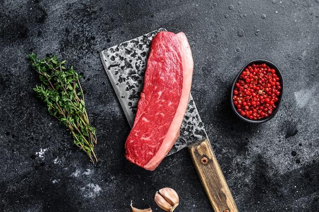 Stek z mięsa wołowego z surowego kapusty na tasaku rzeźniczym. czarne tło. widok z góry.