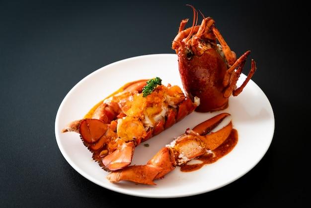 Stek z ogona homara z sosem i jajkami krewetek na białym tle