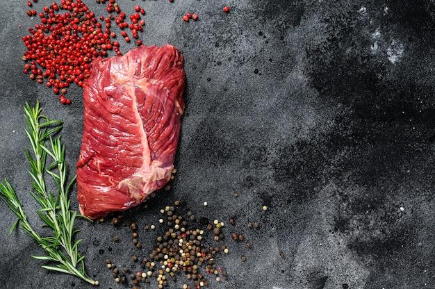 Stek z ostrza, surowe mięso, marmurkowa wołowina. czarne tło.