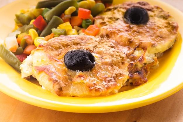 Stek z pieczonego mięsa z roztopionym serem i krążkiem ananasa