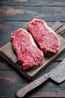 Stek z polędwicy w paski, surowe marmurkowe mięso wołowe, na starym drewnianym stole, z miejscem na kopię tekstu