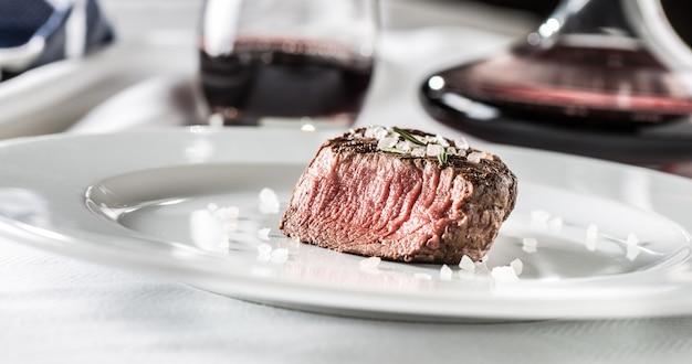 Stek z polędwicy wołowej na białym talerzu i czerwonego wina w pubie lub restauracji.