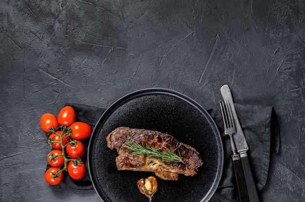 Stek z polędwicy wołowej na czarnym tle. miejsce na tekst. marmurowa wołowina
