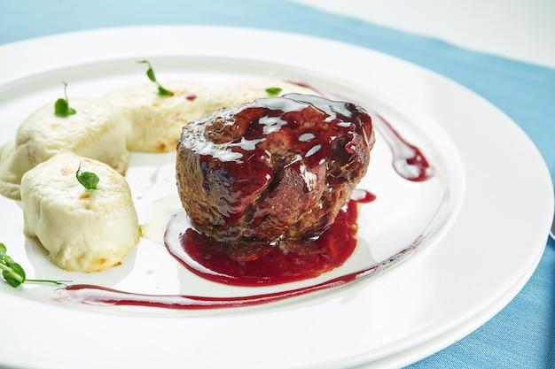 Stek z polędwicy wołowej średnio krwisty z sosem jagodowym i kluseczkami ziemniaczanymi na białym talerzu na niebieskim obrusie