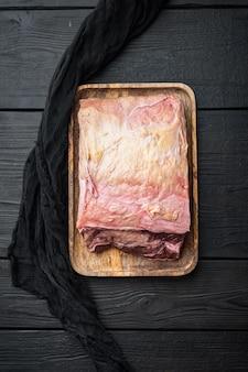 Stek z polędwicy wołowej, surowe mięso wołowe pokrojone, na czarnym drewnianym tle, widok z góry