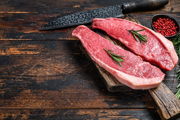 Stek z polędwicy wołowej surowego mięsa cap na desce do krojenia. ciemne tło drewniane. widok z góry. skopiuj miejsce.