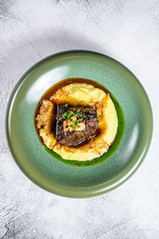 Stek z polędwicy wołowej z boczkiem z tłuczonymi ziemniakami.