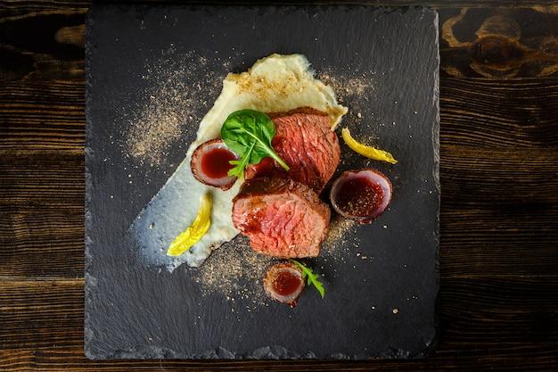 Stek z polędwicy wołowej z czerwonym sosem i puree ziemniaczanym na talerzu łupkowym