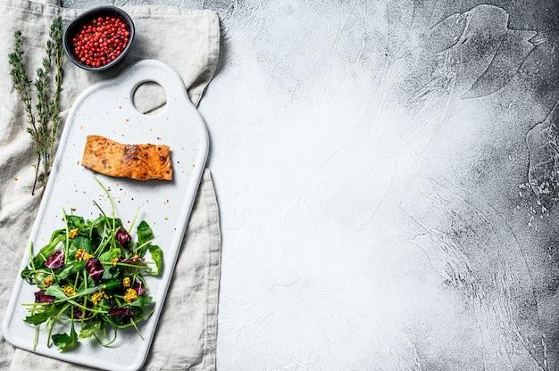 Stek z pstrąga z rukolą, sałatą i żurawiną. widok z góry.