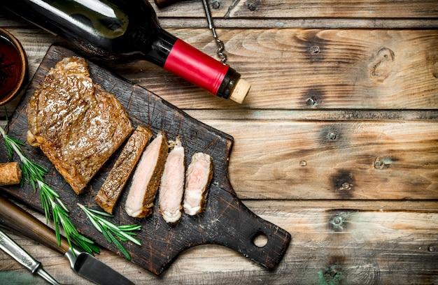 Stek z rostbefu z czerwonym winem. na drewnianym tle.