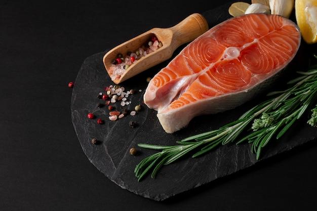 Stek z ryby łososia z przyprawami na czarnym tle