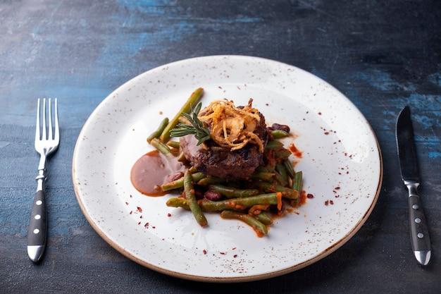 Stek z siekanego mięsa z sosem i chipsami cebulowymi na talerzu podawany z widelcem i nożem