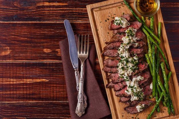Stek z sosem z sera pleśniowego podawany ze szparagami na ciemno.