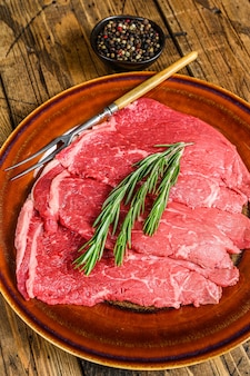 Stek z surowego mięsa cielęcego posiekać na talerzu. drewniane tła. widok z góry.