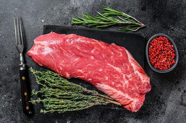 Stek z surowego mięsa wołowego. czarne tło. widok z góry.