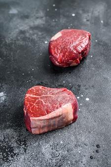 Stek z surowego mięsa wołowego filet z polędwicy. czarne tło. widok z góry.