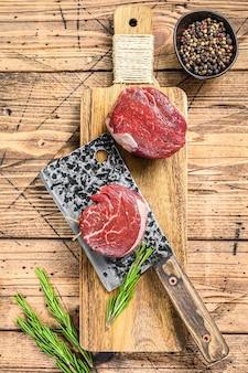 Stek z surowego mięsa wołowego filet z polędwicy. drewniane tło. widok z góry.