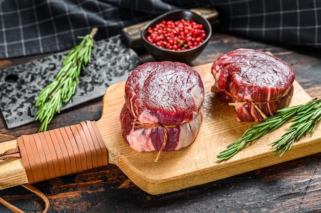 Stek z surowego mięsa wołowego filet z polędwicy na desce do krojenia. ciemne tło drewniane. widok z góry.